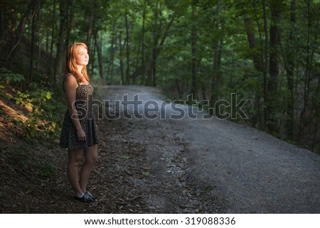 Young woman standing on dark forest path illuminated by evening sunshine - stock photo