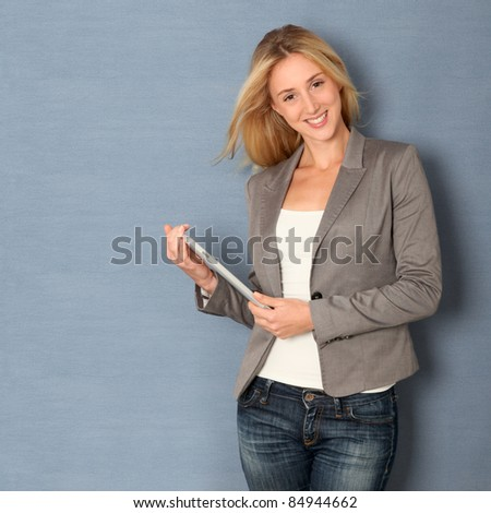 Young woman standing on grey background with touchpad - stock photo