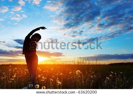 Young woman standing on meadow with herbs on sunset - stock photo