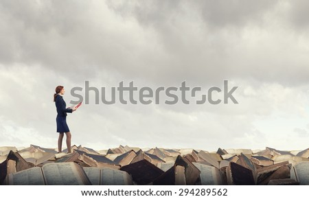 Young woman standing on pile of old books