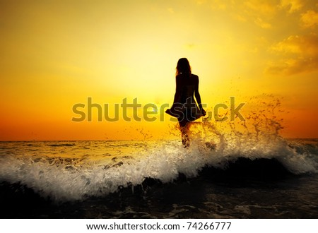 Young woman standing on rock in sea and holding her dress.