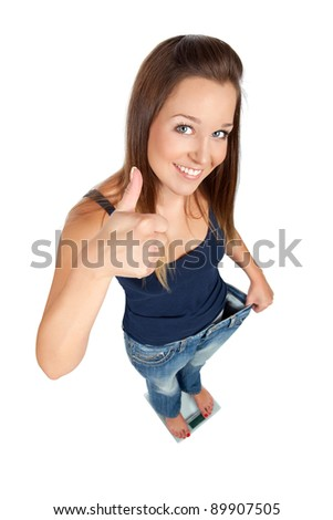 Young woman, standing on scale, satisfied with dieting results. Isolated on white - stock photo