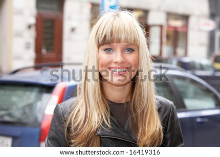 Young woman standing on sidewalk in city, looking at camera, smiling - stock photo