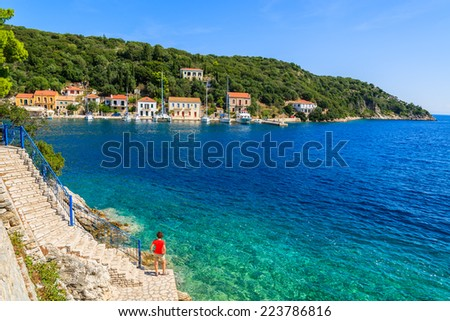 Young woman standing on stone pier in Kioni fishing port, Ithaka island, Greece - stock photo