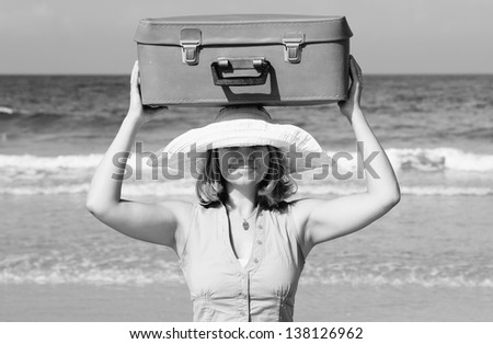 young woman standing on the beach with vintage suitcase - stock photo
