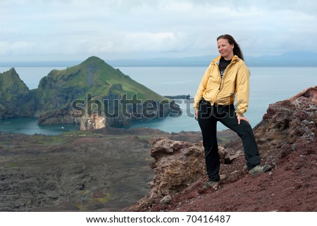 young woman standing on the Eldfell volcano, Westman Islands, Iceland - stock photo