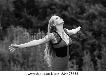 Young woman standing on the fild with her arms outstretched - stock photo