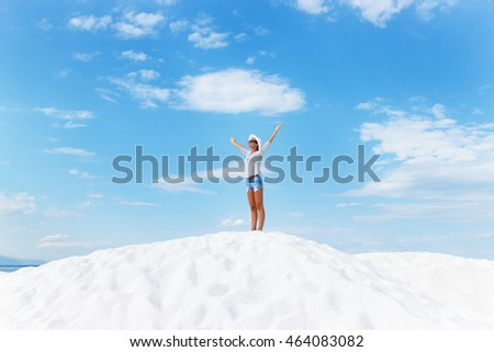Young woman standing on white beach with her arms outstretched over horizon. She is looking towards the sun.