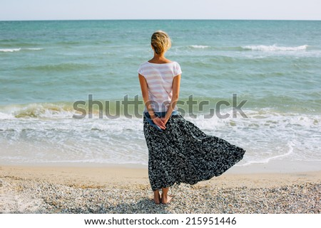 young woman standing on windy beach. back view - stock photo