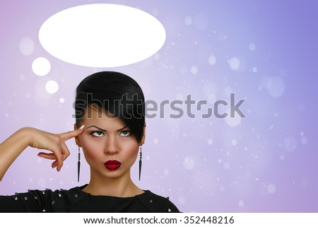 Young woman standing thinking with her finger raised and a grimace of concentration in a humorous stereotypical depiction  - stock photo