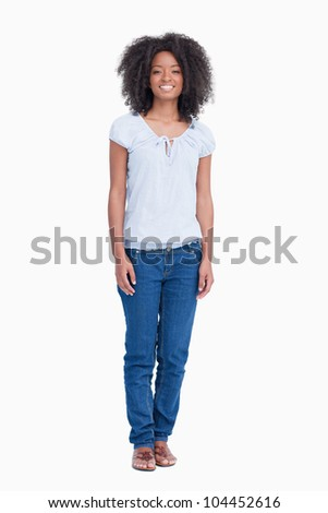 Young woman standing upright while beaming against a white background - stock photo