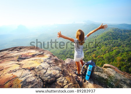 Young woman standing with backpack on cliff's edge and looking to a sky - stock photo
