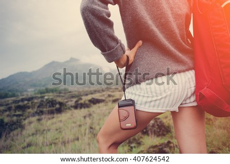 Young woman standing with photo camera near volcano in the wild (intentional sun glare and vintage color) - stock photo