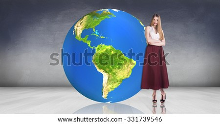 Young woman stands near big earth ball in the gray room.Elements of this image furnished by NASA - stock photo