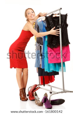 Young woman stands near her clothes rack with lots of dresses,and embraces clothes. - stock photo