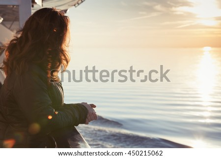 Young woman stands on the deck of cruise ship and starring at the setting sun, close-up silhouette portrait with natural lens glow effect