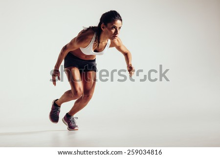 Young woman starting to run and accelerating over grey background. Powerful young female athlete running in competition. - stock photo