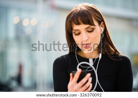 Young woman sticking out tongue while making video call in street - stock photo