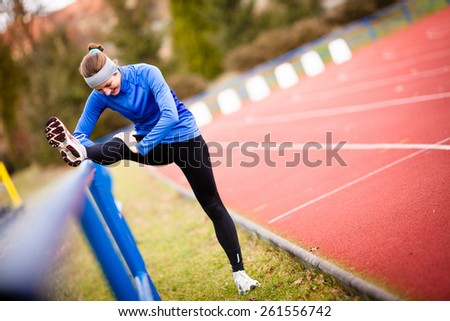 Young woman stretching before her run - stock photo