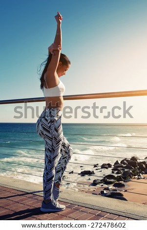 Young woman stretching before her run while standing on wooden jetty with beautiful beach coastline on background,female runner warming up before a workout outdoors at sunny summer day, filtered image - stock photo