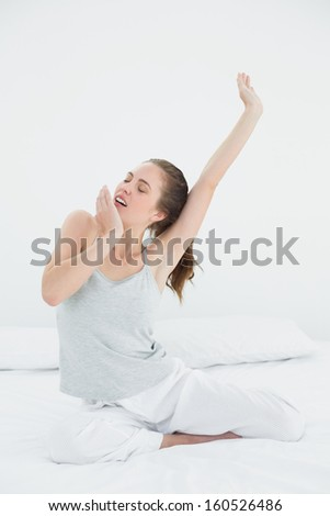 Young woman stretching her arms up while yawning in bed - stock photo