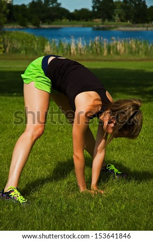 Young woman stretching her hamstrings and lower back, at a city park. - stock photo