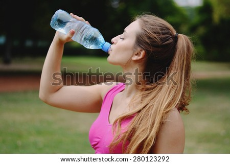 Young woman stretching in the park before Exercise. Caucasian sport fitness model in city park outdoors. - stock photo