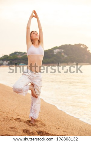 Young woman stretching on sea background. - stock photo