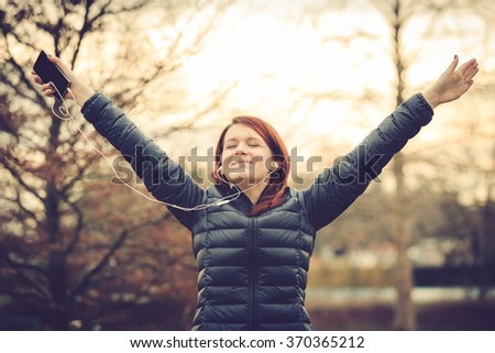 Young Woman stretching outdoor in a city park listening to music.Female fitness outside doing stretch exercises in morning before a run. - stock photo