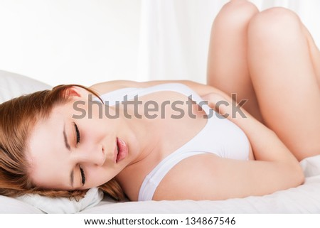 Young woman stroking her belly because of bellyache lying on bed - stock photo