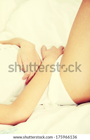 Young woman stroking her belly becouse of bellyache - stock photo