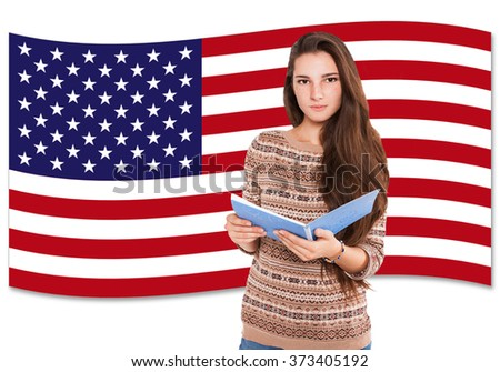 Young woman student beautifully smiling, holding notebooks on the background with flag of the USA. English language learning concept