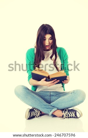 Young woman student sitting and reading a book. - stock photo