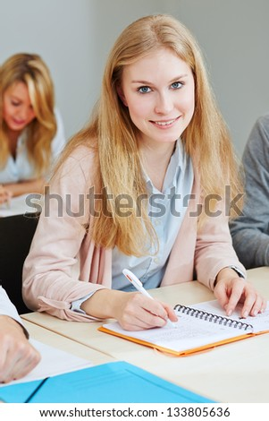 Young woman studying in university and sitting in lecture - stock photo
