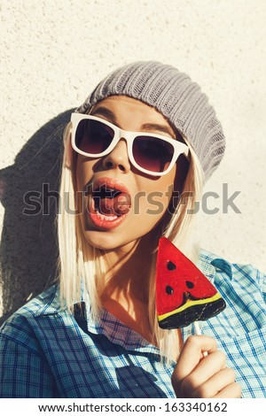 Young woman sucking a lollipop. Cheerful girl in sunglasses and a knitted hat have fun with candy in her hands. Lick mouth. Outdoors, lifestyle. - stock photo