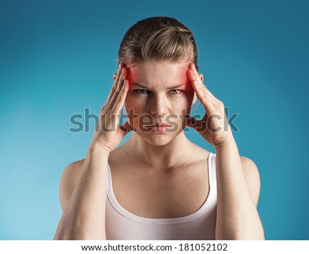 Young woman suffer from dizziness or vertigo holding her head. Portrait of exhausted female with migraine problem over blue background.  - stock photo