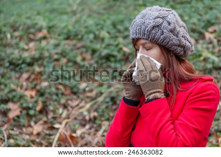 Young woman suffering from a cold or flu blowing her nose on a white paper handkerchief on a forest wearing a red overcoat, a beanie and gloves during winter  - stock photo