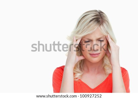 Young woman suffering from a headache against a white background - stock photo