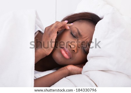 Young woman suffering from headache in bed at home