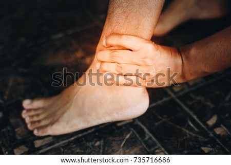 Young woman suffering from pain in ankle while sitting on stretc