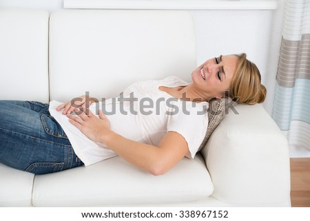 Young woman suffering from stomach pain while lying on sofa at home - stock photo