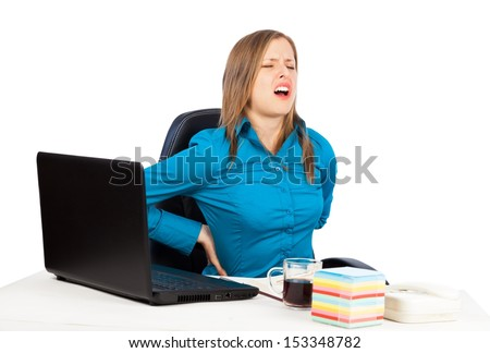 Young woman suffering from terrible back pain at the office. - stock photo