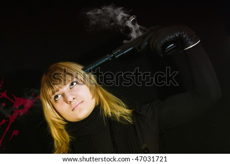 Young woman suicide with pistol on black background