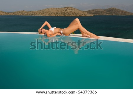 Young woman sunbathing at a swimming pool - stock photo