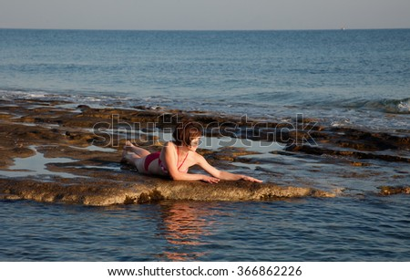 Young woman sunbathing at the seaside - stock photo