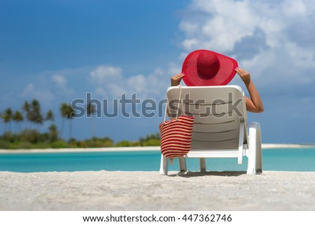 Young woman sunbathing on lounger at tropical beach - stock photo