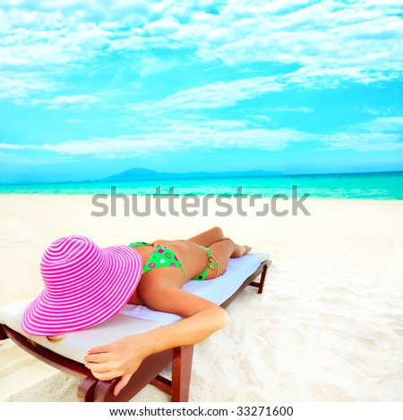 Young woman sunbathing on the chair near the ocean