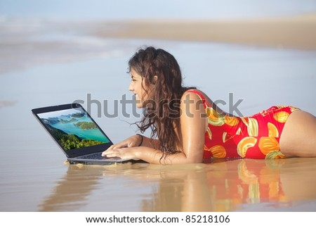 young woman surfing internet with laptop on wet sand - stock photo