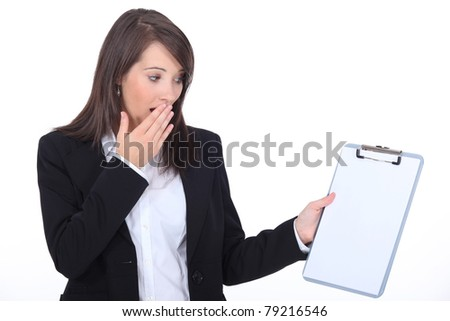 Young woman surprised watching notepad