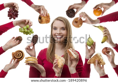 young woman surrounded my many cakes and fruits not sure what to eat - stock photo
